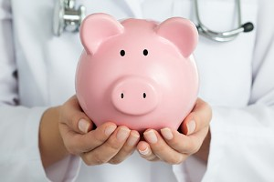 Female Doctor Holding Piggy Bank