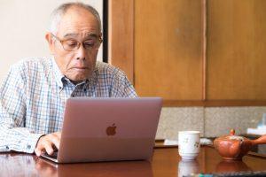 パソコンを触る年配男性