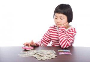 お金と電卓を使う少女