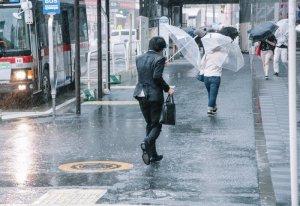 大雨の中を歩く男性