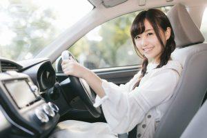 笑顔で運転席に座る女性